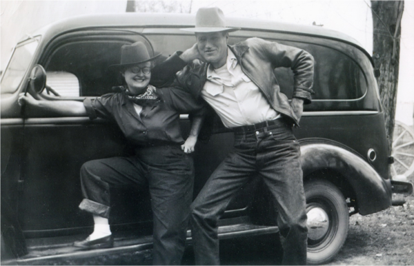 Eileen Blakely and her husband posing in jeans and fedoras in front of a 1950s era car.